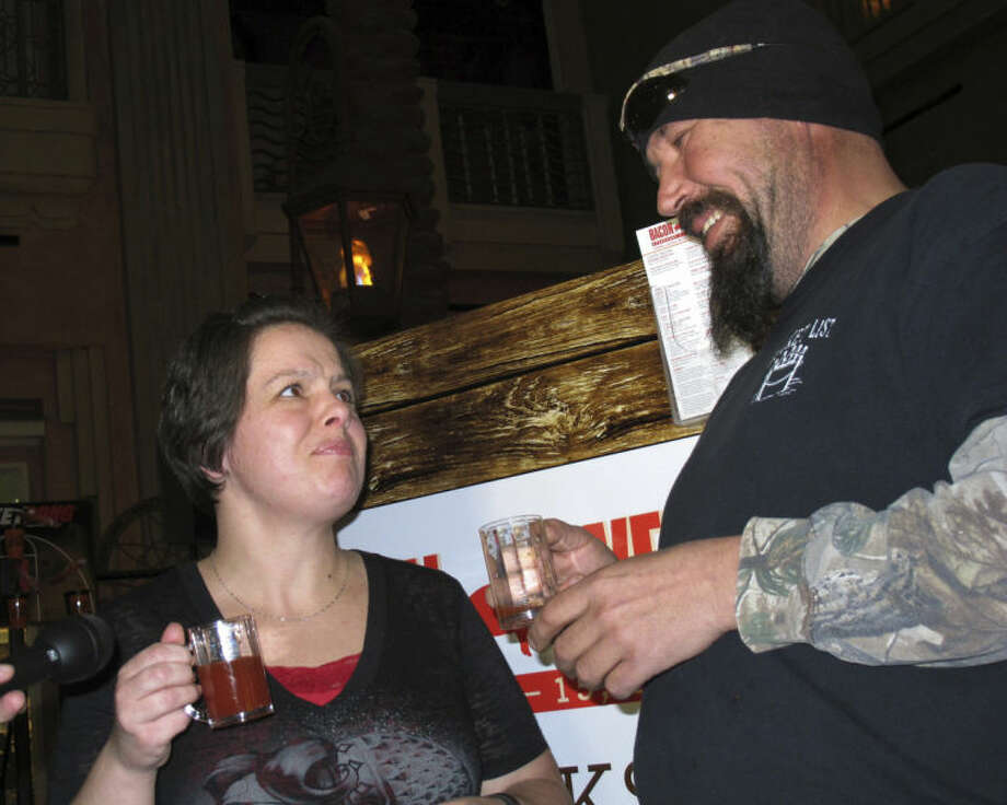 Carrie Jorgenson, left, and her husband Mike, right, react after trying bacon-flavored Bloody Mary drinks, Monday, Feb. 10, 2014 at the Tropicana Casino and resort in Atlantic City, N.J. The casino's Bacon Week festival includes unusual offerings like bacon milk shakes, bacon cupcakes, bacon bloody Marys, beer, vodka and bourbon, and even bacon-flavored toothpaste, dental floss and lip balm. (AP Photo/Wayne Parry)