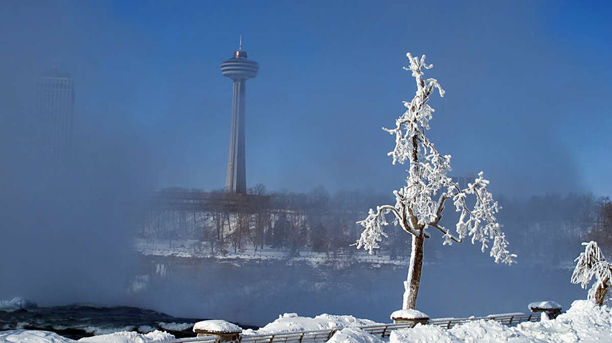 The tower in Niagara Falls, Ontario is flanked by the misty brink of the American Falls as viewed from Niagara Falls, N.Y., on Friday, Feb. 20, 2015 . Although sections of the three waterfalls that make up the natural attraction appear to have frozen in place, the Niagara River continues to flow over the precipice to the Arctic-like buildup below. (AP Photo/Carolyn Thompson)