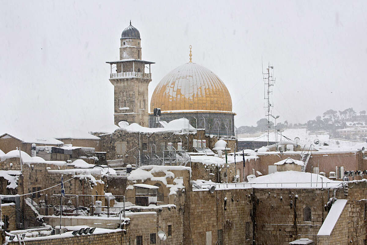 The Dome of the Rock Mosque in the Al Aqsa Mosque compound is seen in Jerusalem's old city, Friday, Feb. 20, 2015. A heavy winter storm descended on parts of the Middle East on Friday, with snow forcing the closure of all roads leading in and out of Jerusalem and sprinkling Israel's desert with a rare layer of white. (AP Photo/Sebastian Scheiner)