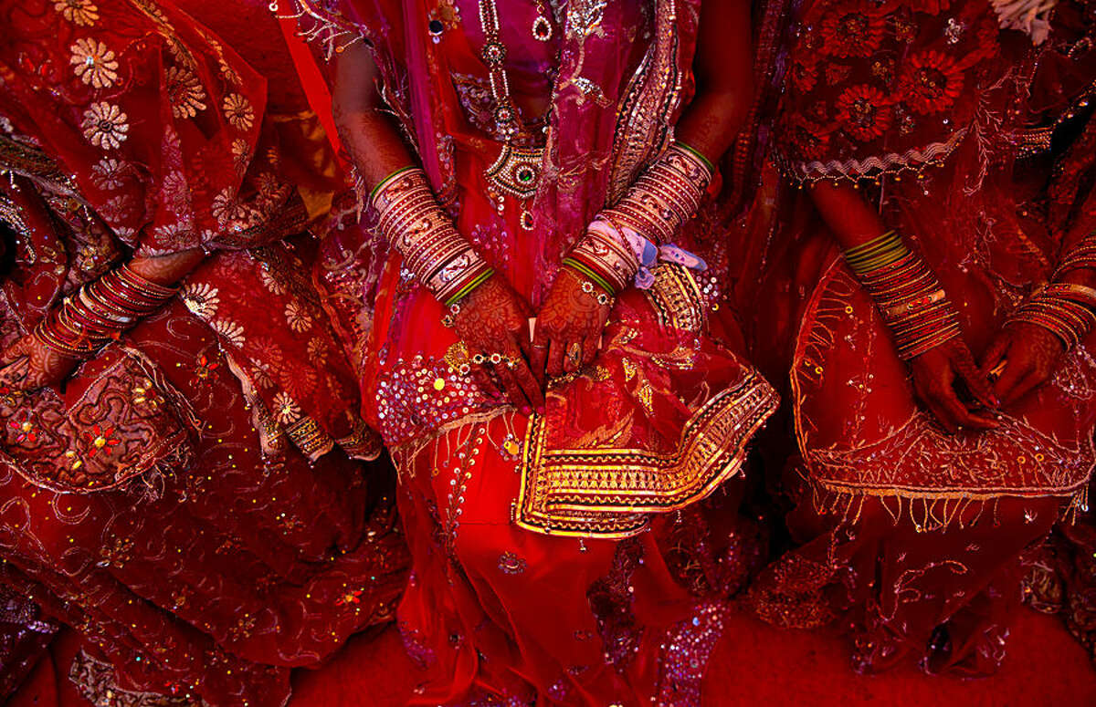 Indian brides from impoverished families, dressed in wedding finery, wait for their grooms to arrive during a mass marriage ceremony in New Delhi, India, Friday, Feb. 20, 2015. 12 couples tied the knot in a single ceremony organized by a social organization, that would otherwise have cost each family thousands of dollars. (AP Photo/Saurabh Das)