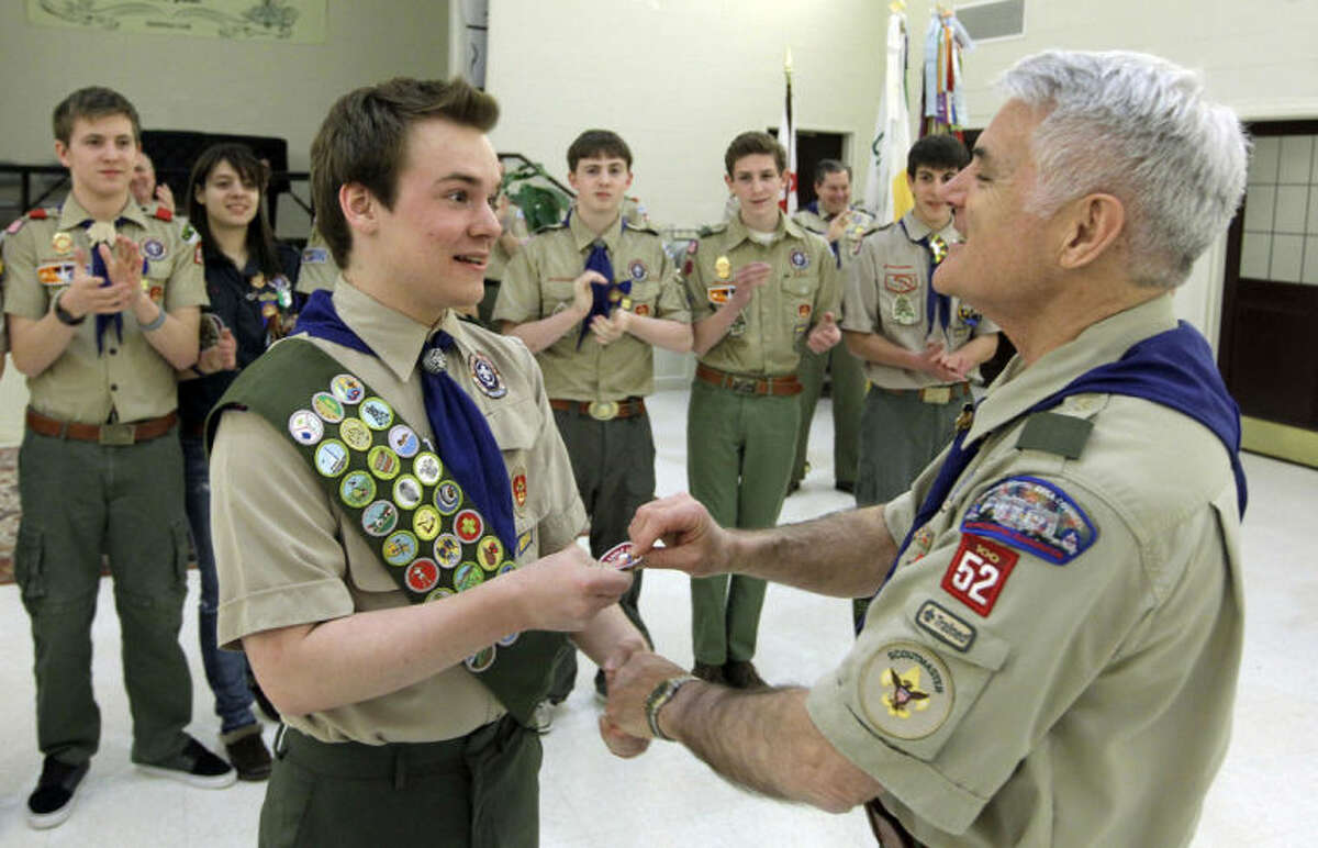 Pascal Tessier, left, a gay Boy Scout, receives his Eagle Scout badge from Troop 52 Scoutmaster Don Beckham, Monday, Feb. 10, 2014, in Chevy Chase, Md. Tessier, of Maryland, has become one of the first openly gay scouts to reach the highest rank of Eagle, following a policy change to allow gay youth in the Boy Scouts of America. (AP Photo/Luis M. Alvarez)