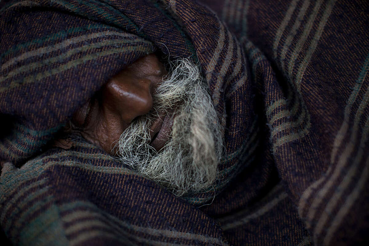 An Indian homeless man sleeps covered in a blanket early morning in the old quarters of Delhi, India, Friday, Feb. 20, 2015. Some 800 million people in the country live in poverty, many of them migrating to big cities in search of a livelihood and often ending up on the streets. (AP Photo/Bernat Armangue)