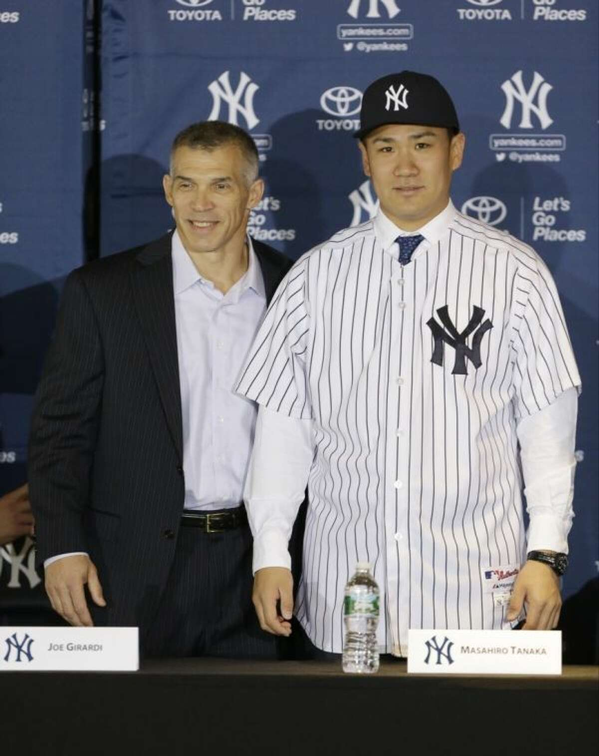 New York Yankees pitcher Masahiro Tanaka, of Japan, poses for photographs with manager Joe Girardi during a news conference at Yankee Stadium Tuesday, Feb. 11, 2014, in New York. (AP Photo/Frank Franklin II)