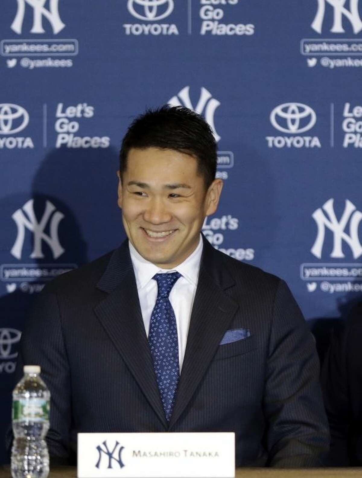 New York Yankees pitcher Masahiro Tanaka, of Japan, smiles as he arrives for a basesball news conference at Yankee Stadium Tuesday, Feb. 11, 2014, in New York. (AP Photo/Frank Franklin II)