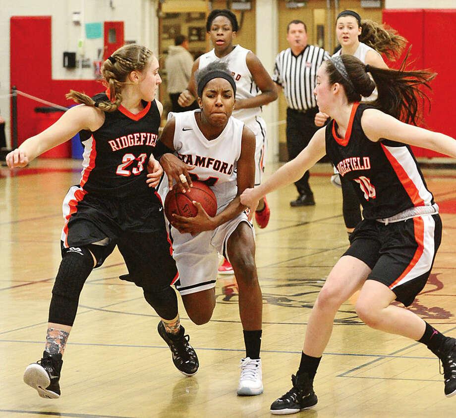 Hour photo / Erik Trautmann Stamford High School battles Ridgefield during the FCIAC Girls Basketball Quarterfinals Saturday at Fairfield Warde High School.