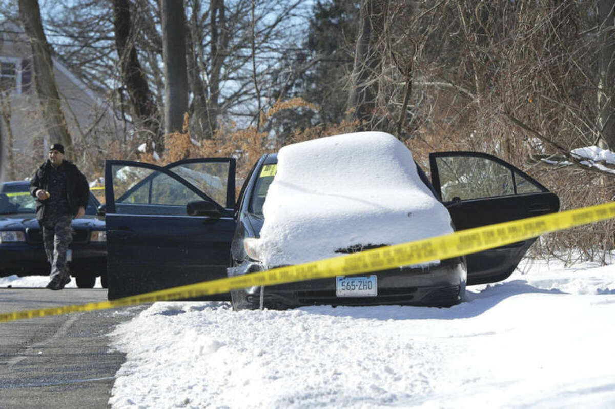 Hour photo / Alex von Kleydorff Police investigate a deceased male who was found in the back seat of this abandoned Toyota on Gray Rock Road in Norwalk Tuesday morning.