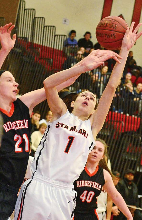 Hour photo / Erik Trautmann Stamford High School's #1 Kelly Jagodrinski battles Ridgefield's #21 Rebecca Lawrence during the FCIAC Girls Basketball Quarterfinals Saturday at Fairfield Warde High School.