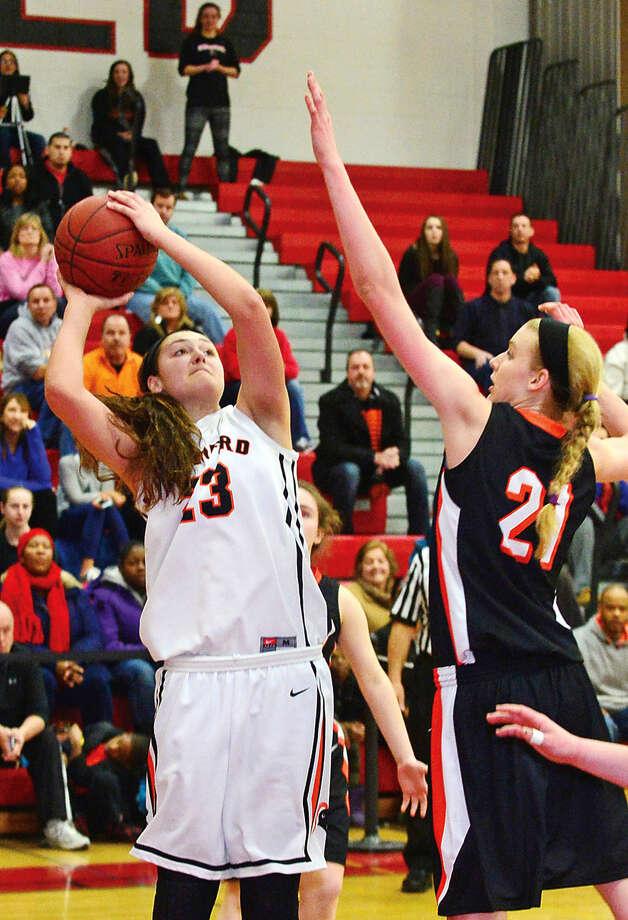 Hour photo / Erik Trautmann Stamford High School's #23 Alexa Kellner battles Ridgefield's #21 Rebecca Lawrence during the FCIAC Girls Basketball Quarterfinals Saturday at Fairfield Warde High School.