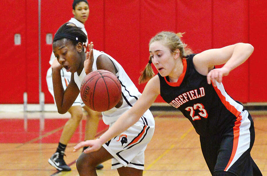 Hour photo / Erik Trautmann Stamford High School's #11 Britney Moise battles Ridgefield's #23 Jessica Camarda during the FCIAC Girls Basketball Quarterfinals Saturday at Fairfield Warde High School.