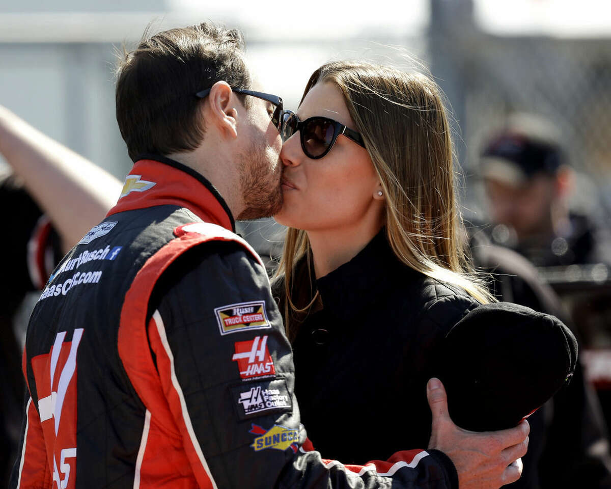 Driver Kurt Busch, left, gives his girlfriend Ashley Van Metre a kiss before getting in his car during qualifying for the Daytona 500 NASCAR Sprint Cup Series auto race at Daytona International Speedway, Sunday, Feb. 15, 2015, in Daytona Beach, Fla. (AP Photo/John Raoux)