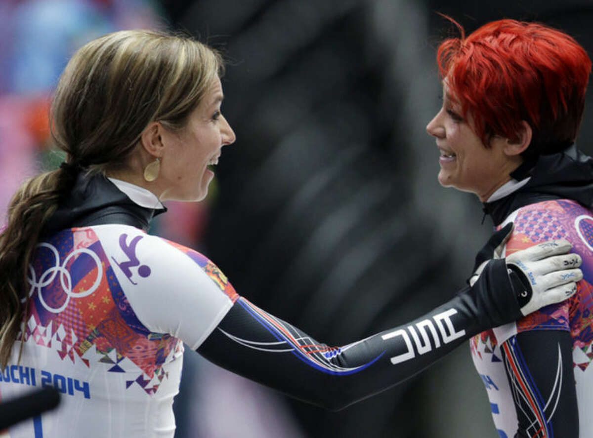 Katie Uhlaender of the United States, right, greets teammate Noelle Pikus-Pace after their third runs during the women's skeleton competition at the 2014 Winter Olympics, Friday, Feb. 14, 2014, in Krasnaya Polyana, Russia. (AP Photo/Natacha Pisarenko)