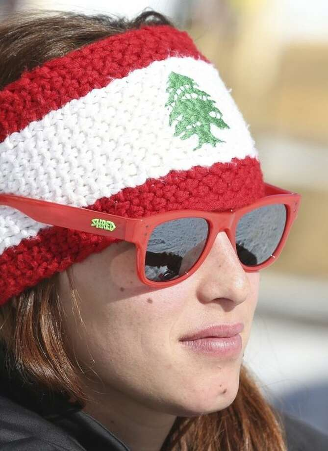 "Lebanon's Jacky Chamoun sits near the alpine ski course finish area at the Sochi 2014 Winter Olympics, Thursday, Feb. 13, 2014, in Krasnaya Polyana, Russia. The Lebanese Olympic skier seen topless in revealing photographs and a video that circulated on the Internet says her country's sports officials are ""on my side."" Three years ago, Chamoun posed for a calendar photo shoot. Behind-the-scenes footage recently was posted online, and Lebanon's Sports and Youth Minister reportedly ordered an investigation. (AP Photo/Luca Bruno)"