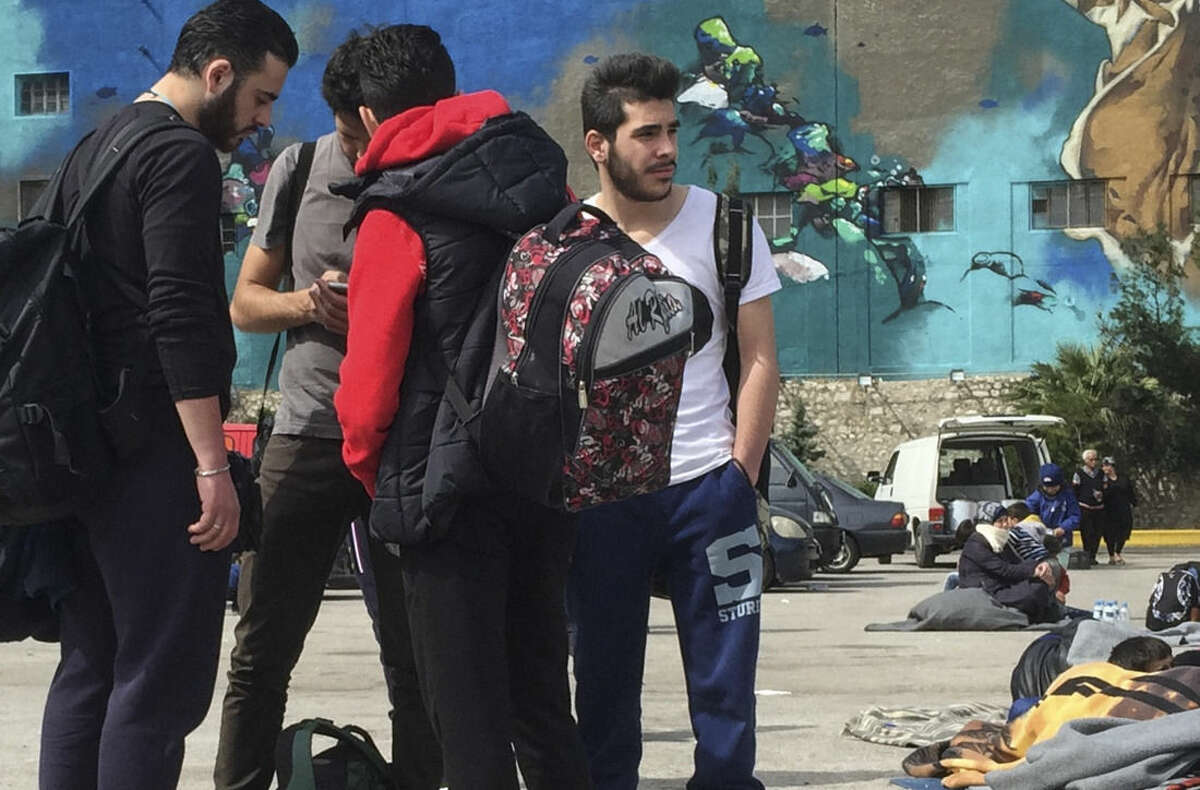 Syrian student Mohammed Sawadi, right, looks across at other migrants at the port of Piraeus, near Athens, on Friday, March 11, 2016.The country's borders were sealed off to migrants and refugees a week ago and NATO expanded patrols in the eastern Aegean Sea _ leaving the continent to wait for signs of arrivals beginning to slow. It's not yet clear if that is happening: From an average of 2,000 arrivals per day at Greek islands facing Turkey so far this year, the numbers have become more uneven. (AP Photo/Derek Gatopoulos)
