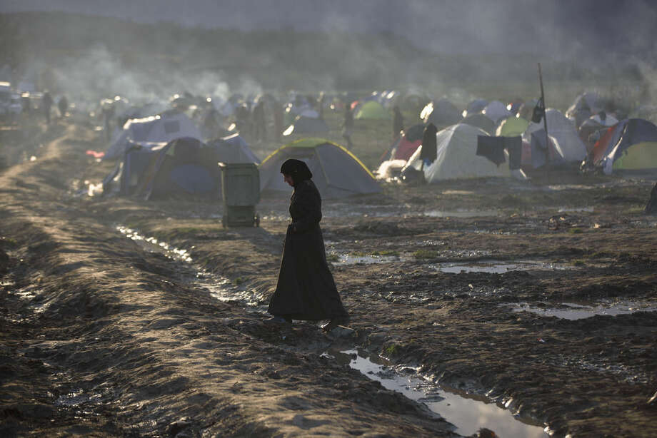 A migrant woman crosses a mud puddle at the northern Greek border station of Idomeni, Friday, March 11, 2016. After nearly three days of rain, conditions in the refugee camp on the Greek-Macedonian where about 14,000 people are stranded have deteriorated significantly, with many of its residents struggling to re-pitch their small camping tents in slightly drier patches. (AP Photo/Visar Kryeziu)