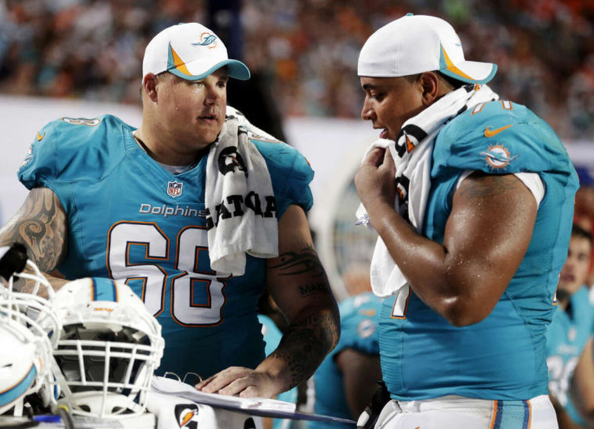 FILE - In this Aug. 24, 2013, file photo, Miami Dolphins guard Richie Incognito (68) and tackle Jonathan Martin (71) look over plays during an NFL preseason football game against the Tampa Bay Buccaneers in Miami Gardens, Fla. Martin was subjected to