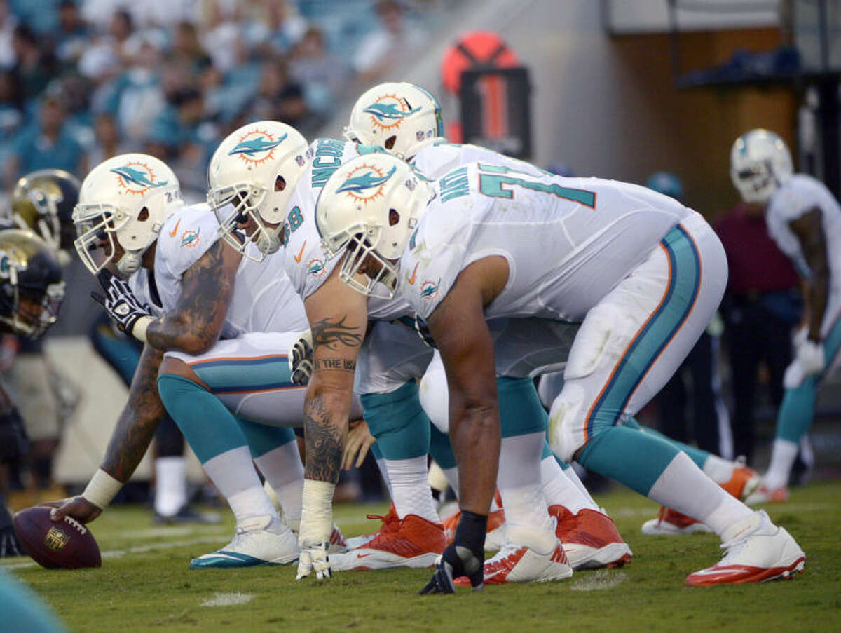 FILE - In this Aug. 9, 2013, file photo, Miami Dolphins center Mike Pouncey, left, guard Richie Incognito (68) and tackle Jonathan Martin (71) set up to block during the first half of an NFL preseason football game against the Jacksonville Jaguars in Jacksonville, Fla. Martin was subjected to