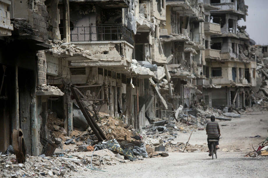 FILE - In this file photo taken on June 5, 2014, a man rides a bicycle through a devastated part of Homs, Syria. Syrian government forces retook the control of Homs in May 2014, after a three year battle with rebels. (AP Photo/Dusan Vranic, File)