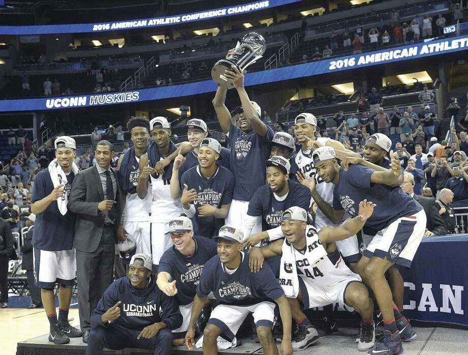 AP photoUConn head coach Kevin Ollie, second from left, poses with his players and the championship trophy after defeating Memphis in the finals of the American Athletic Conference men's tournament on Sunday in Orlando, Fla. Norwalk's Steven Enoch is third from left.