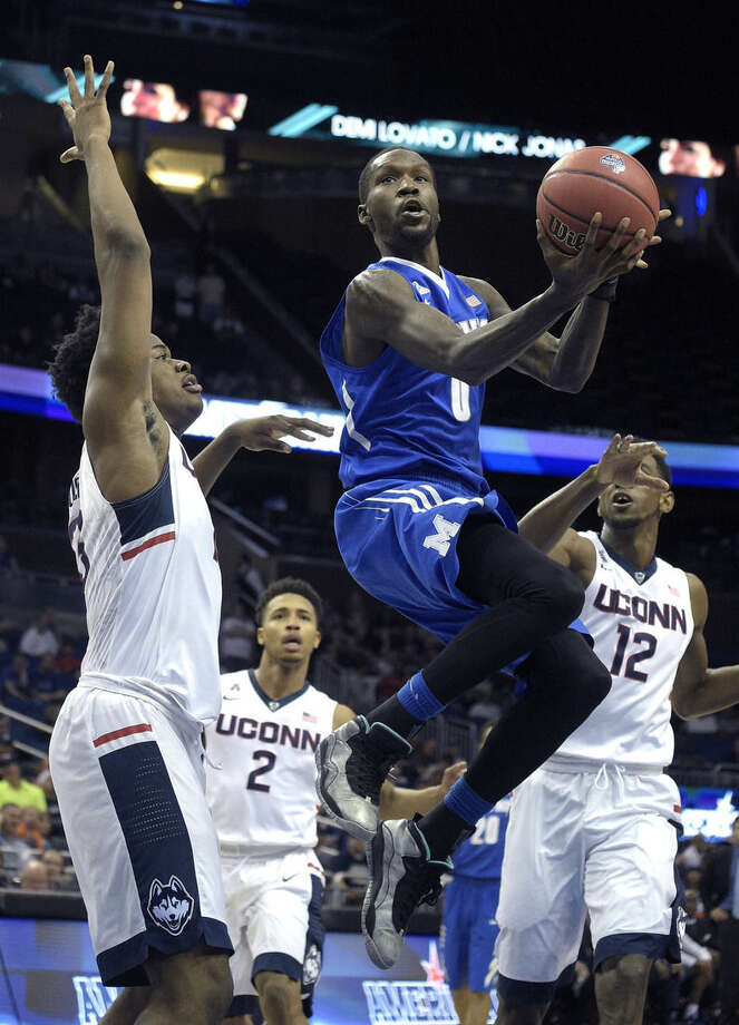 Memphis forward Trashon Burrell (0) goes up for a shot in front of Connecticut forward Steven Enoch (13), left, guard Jalen Adams (2) and forward Kentan Facey (12) during the first half of an NCAA college basketball game in the finals of the American Athletic Conference men's tournament in Orlando, Fla., Sunday, March 13, 2016. (AP Photo/Phelan M. Ebenhack)