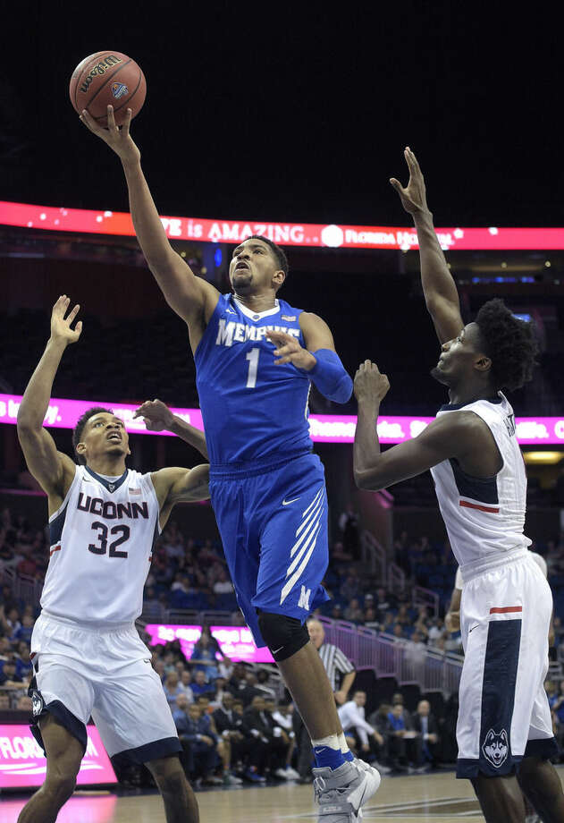 Memphis forward Dedric Lawson (1) goes up for a shot between Connecticut forward Shonn Miller (32) and guard Daniel Hamilton, right, during the first half of an NCAA college basketball game in the finals of the American Athletic Conference men's tournament in Orlando, Fla., Sunday, March 13, 2016. (AP Photo/Phelan M. Ebenhack)