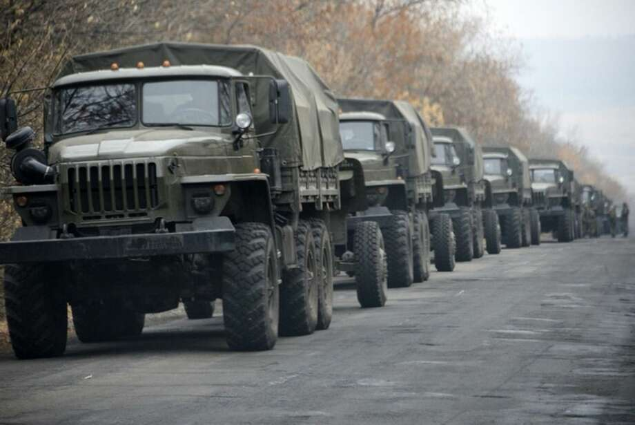 FILE- In this file photo taken Saturday, Nov. 8, 2014, Unmarked military vehicles parked on a road outside the separatist rebel-held eastern Ukrainian town of Snizhne, 80 kilometers (50 miles) from Donetsk, eastern Ukraine. Russia has denied it is sending arms and troops to support the separatists in Ukraine, but dozens of soldiers have been reported killed during drills in the Rostov region of southern Russia, but rights groups have actually attributed the deaths to the conflict over the border in Ukraine. (AP Photo/Mstyslav Chernov, file)