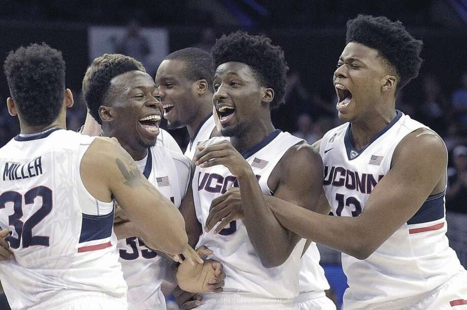 AP photoUConn forward Shonn Miller (32), center Amida Brimah (35), guard Daniel Hamilton (5) and forward Steven Enoch (13) of Norwalk celebrate after defeating Memphis 72-58 in the finals of the American Athletic Conference men's tournament on Sunday in Orlando, Fla.