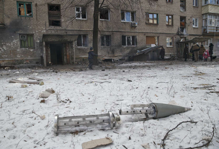 The remains of a rocket lie outside a damaged apartment building in Debaltseve, Ukraine, Friday, Feb. 20, 2015. After weeks of relentless fighting, the embattled Ukrainian rail hub of Debaltseve fell Wednesday to Russia-backed separatists, who hoisted a flag in triumph over the town. The Ukrainian president confirmed that he had ordered troops to pull out and the rebels reported taking hundreds of soldiers captive.(AP Photo/Vadim Ghirda)
