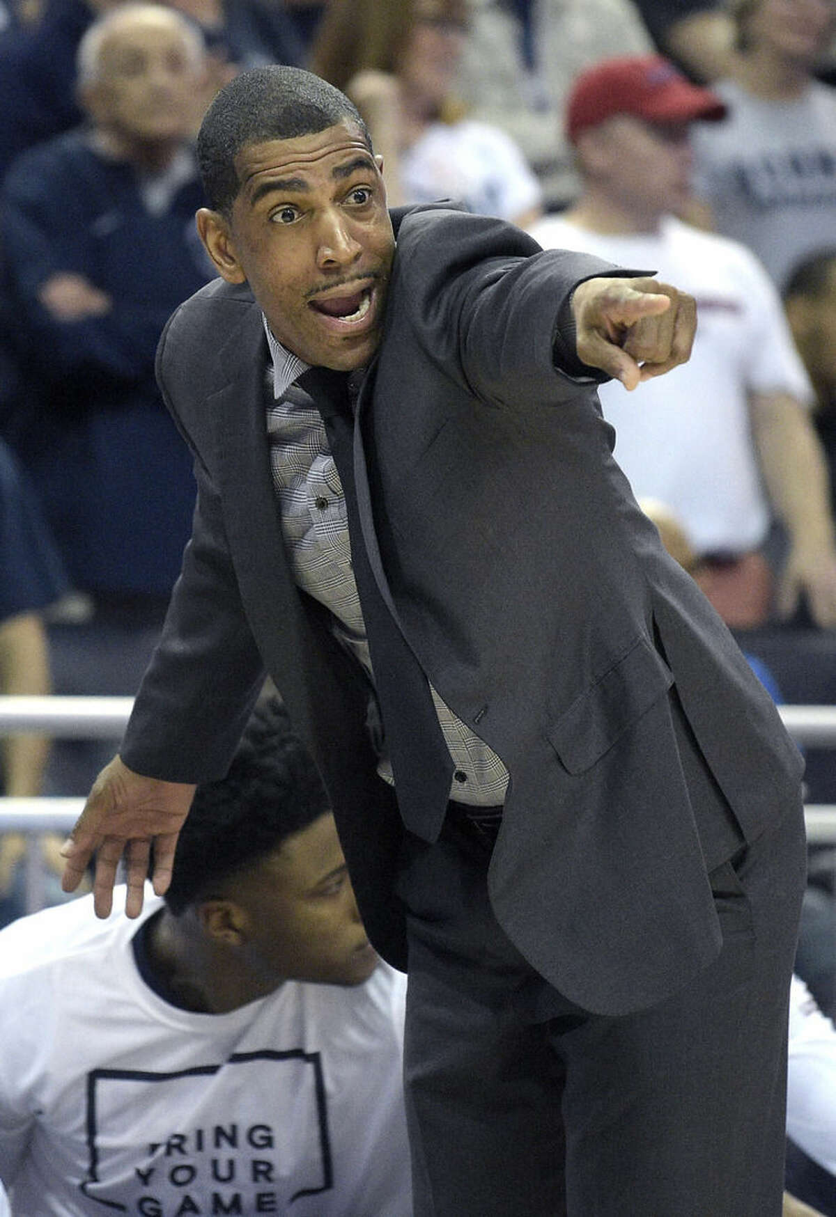 Connecticut head coach Kevin Ollie shouts instructions from the sideline during the first half of an NCAA college basketball game against Memphis in the finals of the American Athletic Conference men's tournament in Orlando, Fla., Sunday, March 13, 2016. (AP Photo/Phelan M. Ebenhack)