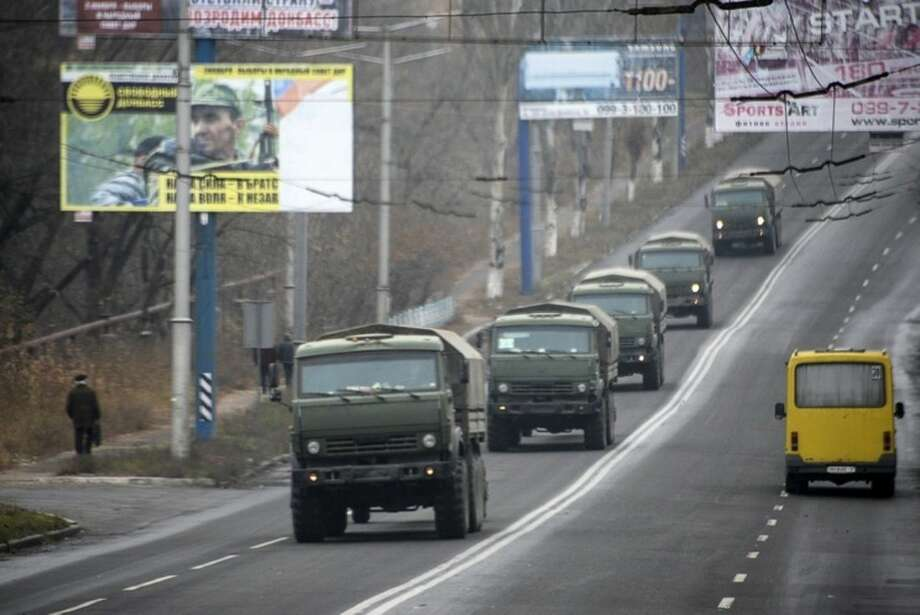 FILE- In this file photo dated Saturday, Nov. 8, 2014, Unmarked military vehicles travel along a road outside the separatist rebel-held town Makiivka, 25 km (16 miles) from Donetsk, eastern Ukraine. Russia has denied it is sending arms and troops to support the separatists in Ukraine, but dozens of soldiers have been reported killed during drills in the Rostov region of southern Russia, but rights groups have actually attributed the deaths to the conflict over the border in Ukraine. (AP Photo/Mstyslav Chernov, file)