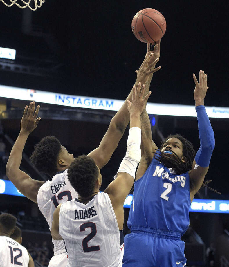 Memphis forward Shaq Goodwin (2) goes up for a shot in front of Connecticut forward Steven Enoch (13) and guard Jalen Adams (2) during the first half of an NCAA college basketball game in the finals of the American Athletic Conference men's tournament in Orlando, Fla., Sunday, March 13, 2016. (AP Photo/Phelan M. Ebenhack)