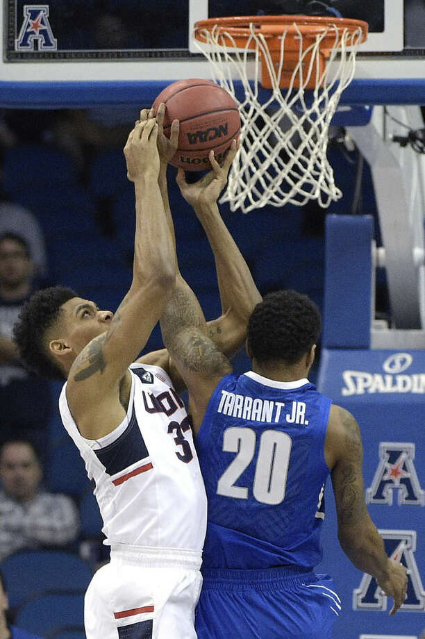 Connecticut forward Shonn Miller (32) and Memphis guard Ricky Tarrant Jr. (20) fight for a rebound during the first half of an NCAA college basketball game in the finals of the American Athletic Conference men's tournament in Orlando, Fla., Sunday, March 13, 2016. (AP Photo/Phelan M. Ebenhack)