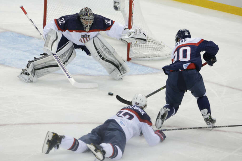 USA goaltender Jonathan Quick defends his goal against Slovakia forward Tomas Tatar as =22= slides across the ice during the 2014 Winter Olympics men's ice hockey game at Shayba Arena, Thursday, Feb. 13, 2014, in Sochi, Russia. (AP Photo/Matt Slocum)