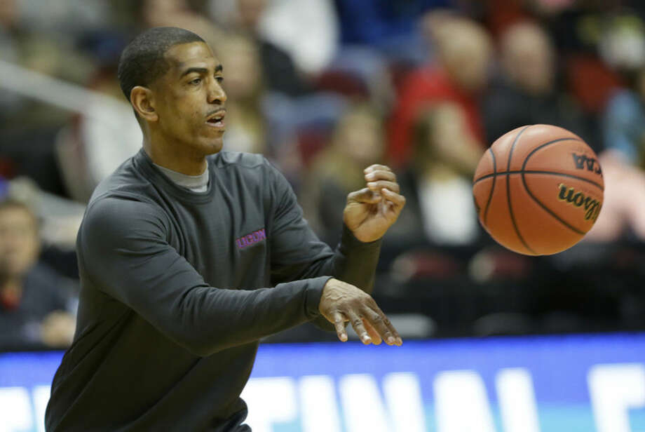 Connecticut head coach Kevin Ollie passes the ball during practice for a first-round men's college basketball game in the NCAA Tournament , Wednesday, March 16, 2016, in Des Moines, Iowa. Connecticut will play Colorado on Thursday. (AP Photo/Charlie Neibergall)