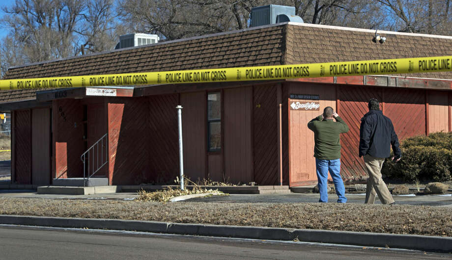 FILE - In this Jan. 6, 2015 file photo, Colorado Springs, Colo., police officers investigate the scene of an explosion at a building in Colorado Springs that houses a barber shop and the Colorado Springs chapter of the NAACP. A law enforcement source says 44-year-old Thaddeus Murphy has been arrested in connection with the explosion and was in custody Friday, Feb. 20, 2015, and due to appear in federal court later in the day. The FBI investigated the explosion as a possible hate crime. (AP Photo/The Colorado Springs Gazette, Christian Murdock, File) MAGS OUT