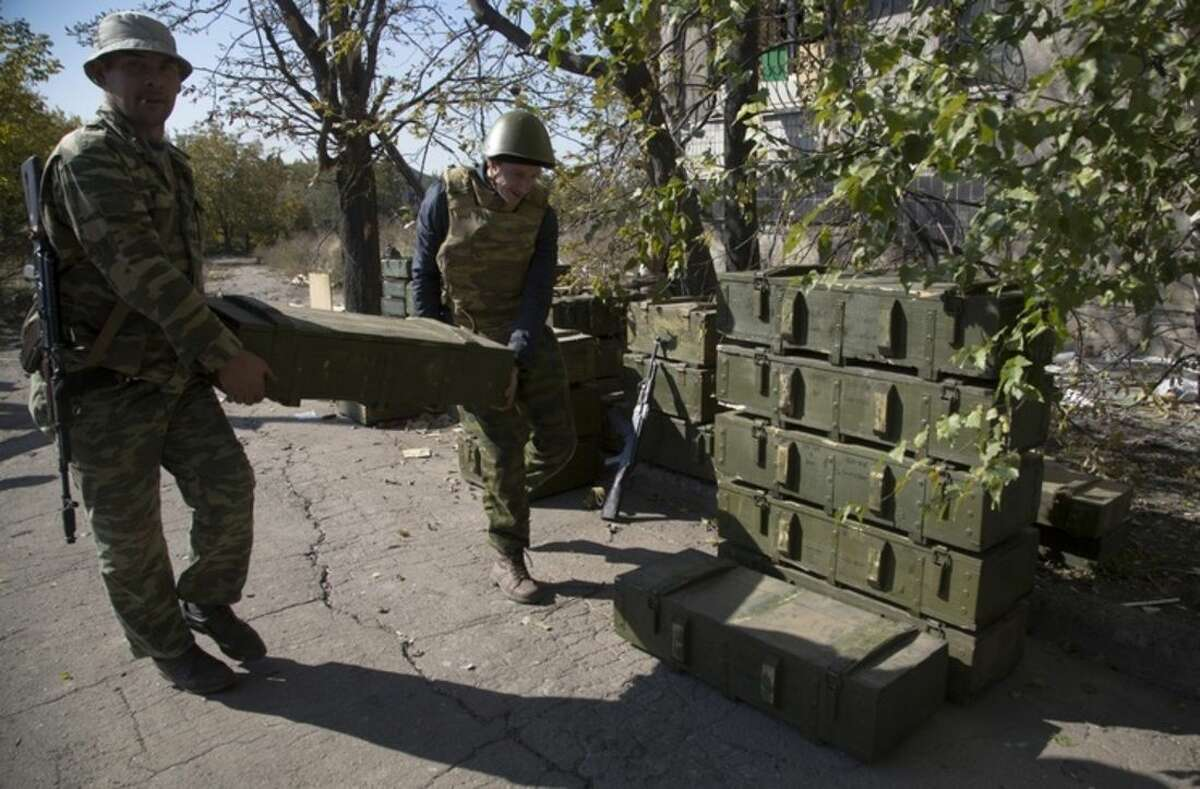 FILE - In this Thursday Oct. 9, 2014, file photo, Pro-Russian rebels carry boxes of munitions at their position near to the airport in the town of Donetsk, eastern Ukraine. Russia has denied it is sending arms and troops to support the separatists in Ukraine, but dozens of soldiers have been reported killed during drills in the Rostov region of southern Russia, but rights groups have actually attributed the deaths to the conflict over the border in Ukraine. (AP Photo/Dmitry Lovetsky, file)