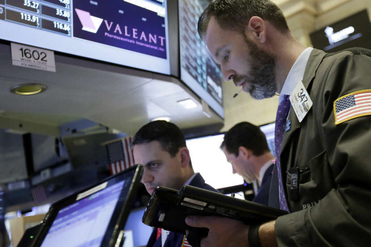 Trader Thomas Cicciari, right, works at the post that handles Valeant Pharmaceuticals on the floor of the New York Stock Exchange, Tuesday, March 15, 2016. Embattled Valeant Pharmaceuticals fell short of profit expectations in the fourth quarter and slashed its guidance for the current quarter and the full year, citing lower sales across many of its businesses. Shares dropped 27 percent in morning trading Tuesday. (AP Photo/Richard Drew)