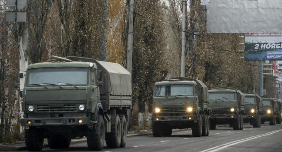 FILE- In this file photo dated Tuesday, Nov. 11, 2014, A convoy of unmarked military vehicles in Donetsk, eastern Ukraine. Russia has denied it is sending arms and troops to support the separatists in Ukraine, but dozens of soldiers have been reported killed during drills in the Rostov region of southern Russia, but rights groups have actually attributed the deaths to the conflict over the border in Ukraine. (AP Photo/Mstyslav Chernov, file)
