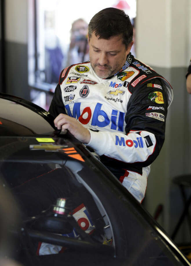 Driver Tony Stewart climbs in his car before practice for the NASCAR Sprint Unlimited auto race at Daytona International Speedway in Daytona Beach, Fla., Friday, Feb. 14, 2014. Stewart has not raced in more than six months since he broke two bones in his leg in an August 2013 sprint-car crash.(AP Photo/John Raoux)