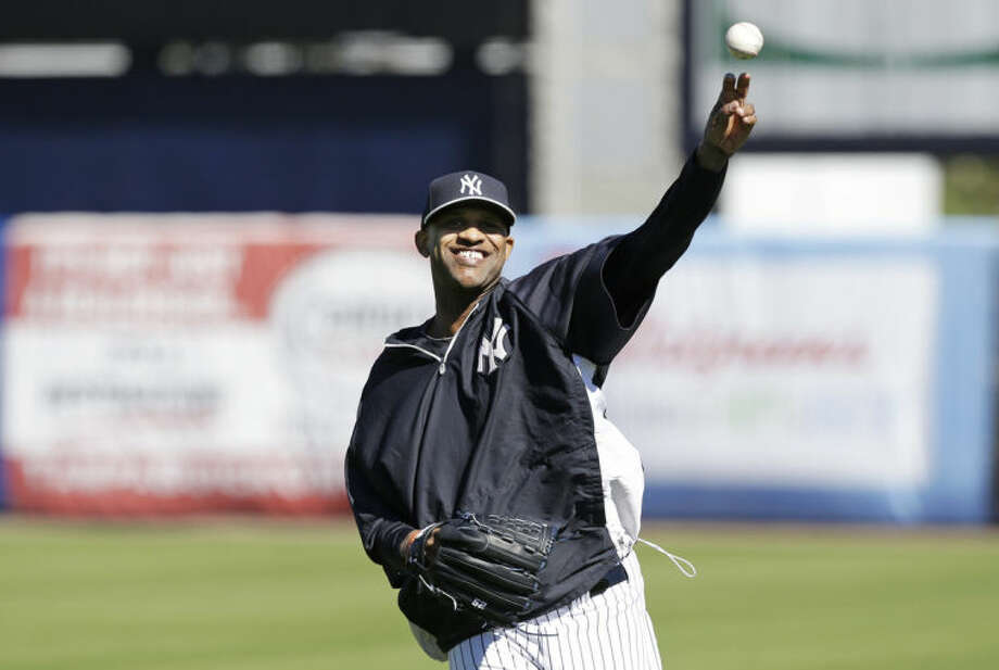 New York Yankees starting pitcher CC Sabathia throws in the outfield during spring training baseball practice Friday, Feb. 14, 2014, in Tampa, Fla. (AP Photo/Charlie Neibergall)