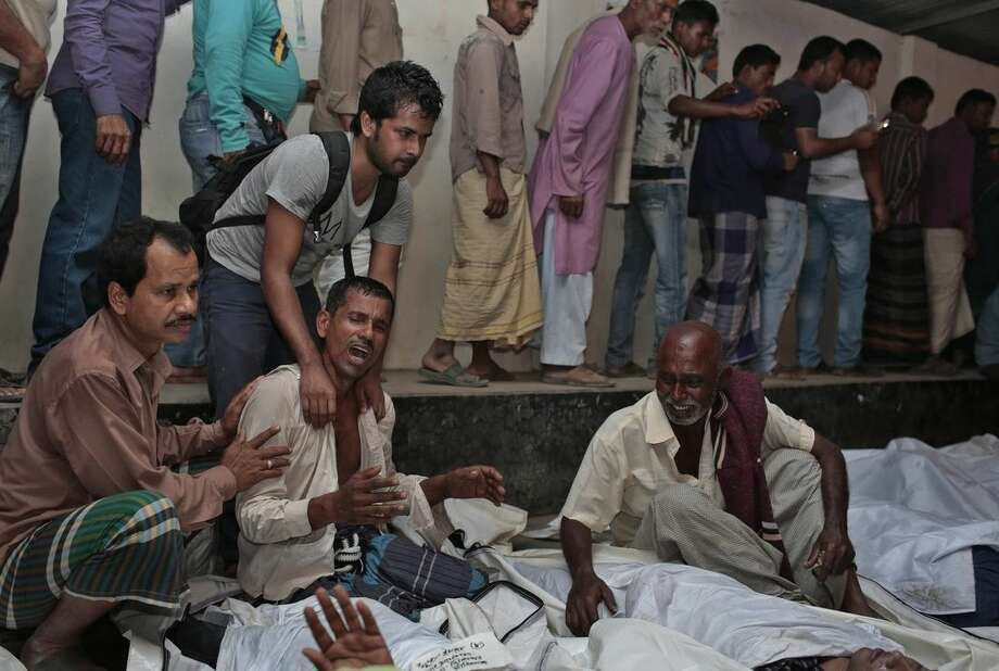 Bangladeshi relatives wail near bodies of victims after a river ferry carrying about 100 passengers capsized Sunday after being hit by a cargo vessel,in Manikganj district, about 40 kilometers (25 miles) northwest of Dhaka, Bangladesh, Sunday, Feb. 22, 2015. It is yet not clear how many people are missing.(AP Photo/ A.M. Ahad)
