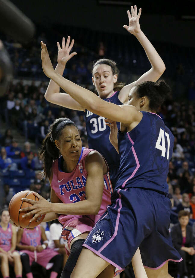 Tulsa guard Ashley Clark (23) is defended by Connecticut forward Breanna Stewart (30) and center Kiah Stokes (41) in the second half of NCAA college basketball game in Tulsa, Okla., Saturday, Feb. 21, 2015. Connecticut won 92-46. (AP Photo/Sue Ogrocki)
