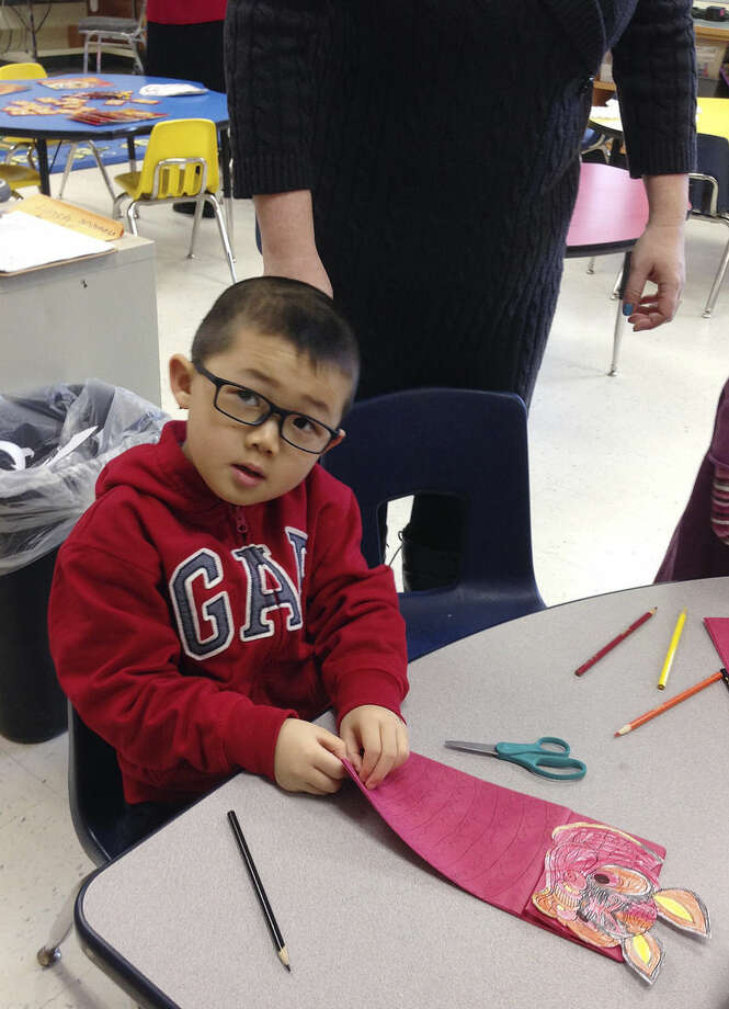 In this Feb. 19, 2015 photo, student Ben Li decorates a dragon puppet to be used in a parade celebrating the Lunar New Year at the Mohegan Elementary School in Montville, Conn. At Connecticut's casinos, the staff can speak to you in nearly any Asian language. The diversity of the workforce at the casinos, which cater heavily to Asian gamblers from New York, is changing the complexion of nearby public schools that have been hiring more language specialists and adding new cultural traditions. (AP Photo/Michael Melia)