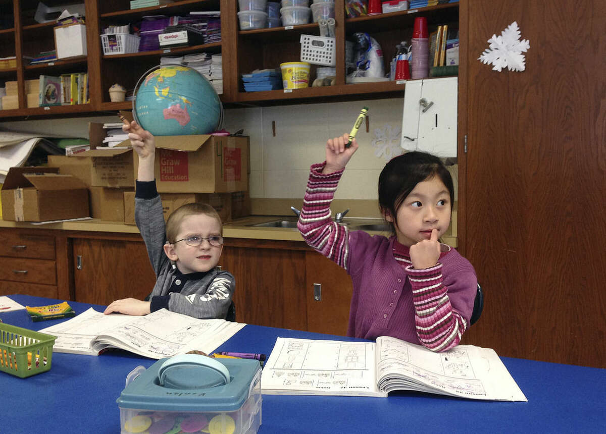 In this Feb. 19, 2015 photo, from left, Solomon Zilbershteyn and Yong Lin Li receive language instruction at the Mohegan Elementary School in Montville, Conn. At Connecticut's casinos, the staff can speak to you in nearly any Asian language. The diversity of the workforce at the casinos, which cater heavily to Asian gamblers from New York, is changing the complexion of nearby public schools that have been hiring more language specialists and adding new cultural traditions. (AP Photo/Michael Melia)