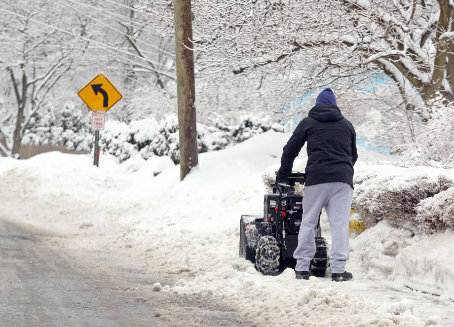 A man uses his snow blower on Tierney Street in Norwalk after the snow storm Sunday morning. Hour Photo / Danielle Calloway