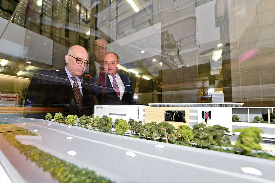 Hour photo / Erik Trautmann Attorneys Bill Hennessey and Larry Cafero look over a large, three-dimensional model of The SoNo Collection shopping mall in the City Hall rotunda Friday morning to be used as part of Norwalk Zoning Commission review of plan.