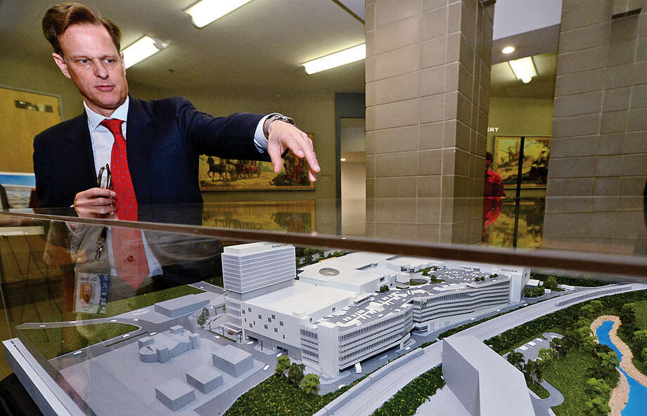Hour photo / Erik Trautmann General Growth Properties Doug Adams unveils a large, three-dimensional model and renderings of The SoNo Collection shopping mall in the City Hall rotunda Friday morning to be used as part of Norwalk Zoning Commission review of plan.