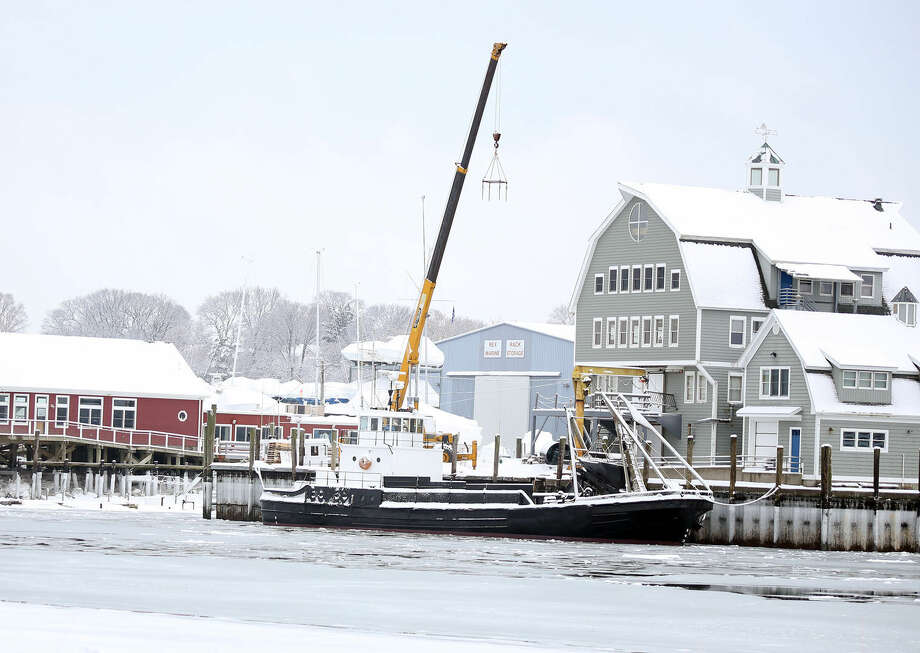 An oyster boat docked in the Norwalk River collects snow Sunday morning. Hour Photo / Danielle Calloway