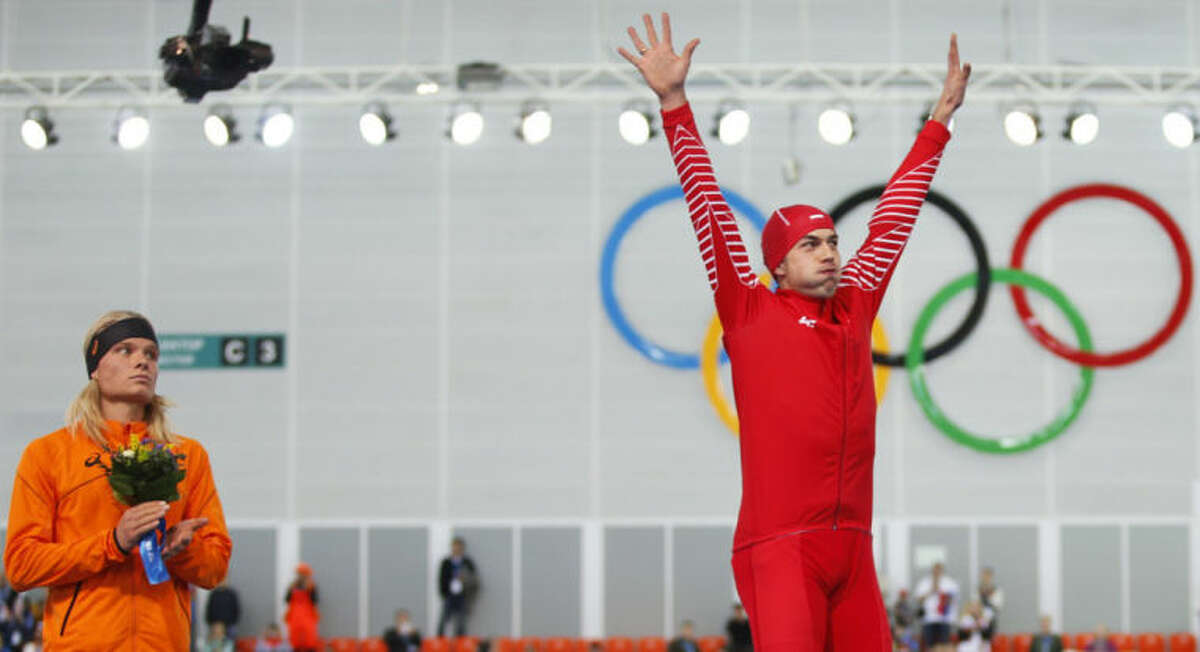 Gold medallist Poland's Zbigniew Brodka, right, acknowledges the crowd as silver medallist Koen Verweij of the Netherlands stands beside him during the flower ceremony for the men's 1,500-meter speedskating race at the Adler Arena Skating Center during the 2014 Winter Olympics in Sochi, Russia, Saturday, Feb. 15, 2014. Verweij lost the gold medal by three thousandth of a second. (AP Photo/Pavel Golovkin)