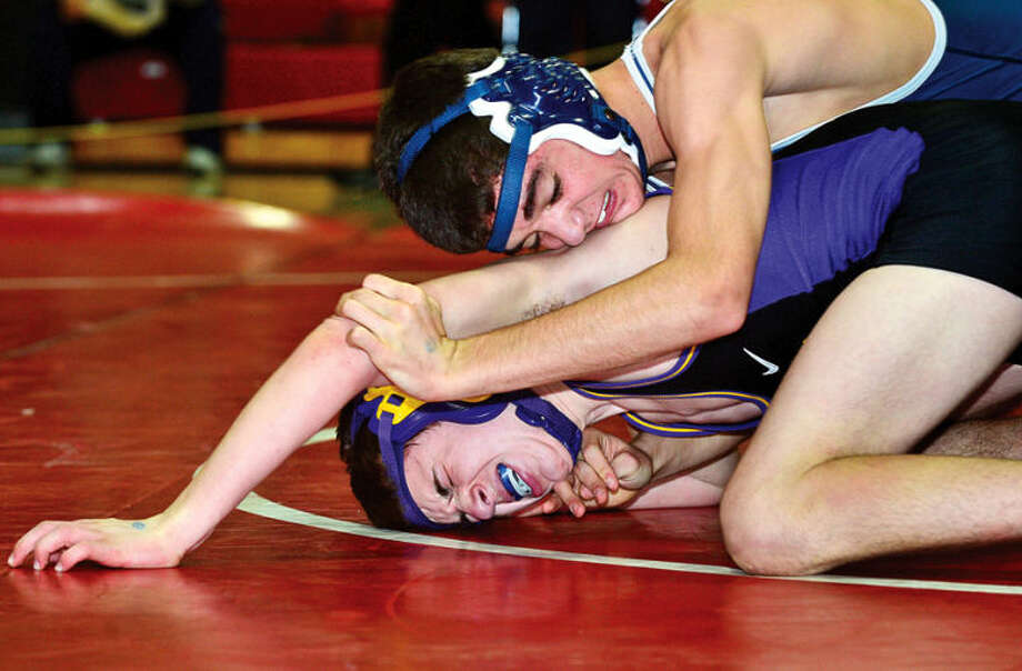 Hour photo / Erik Trautmann Staples's Mat Prior wrestles Westhill's Andrew Blum at 126 in the FCIAC wrestling championship meet at New Canaan High School Saturday.