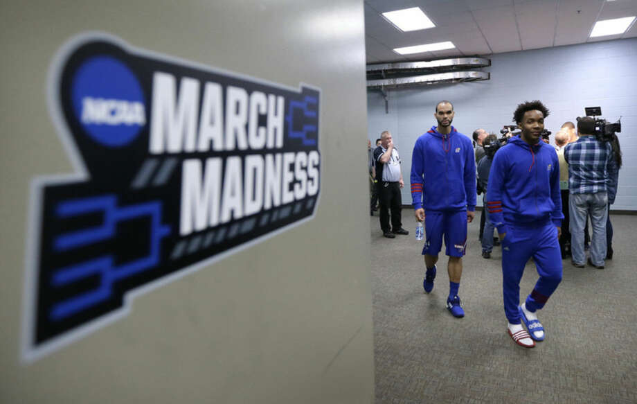 Kansas players Perry Ellis, left, and Devonte' Graham walk to a news conference ahead of a second-round men's college basketball game in the NCAA Tournament, Friday, March 18, 2016, in Des Moines, Iowa. Kansas will play Connecticut on Saturday. (AP Photo/Charlie Neibergall)